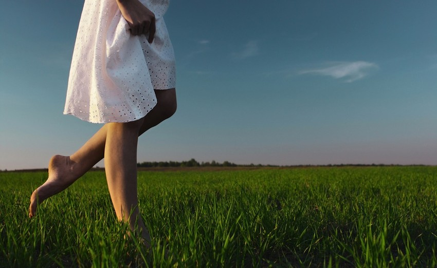 WomanWalkingOnGrassinWhiteDress900-850x522