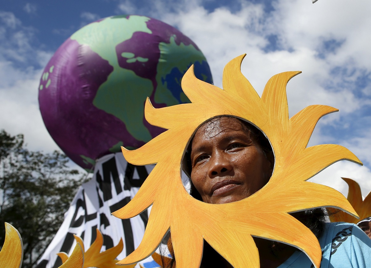"A Filipino environmental activist looks out from a ""sun"" cardboard cutout during a global protest action ahead COP21 summit in Quezon city"