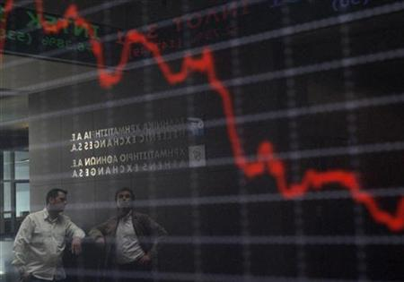 Employees are reflected on an electronic board displaying stock prices at the Athens stock exchange in Athens