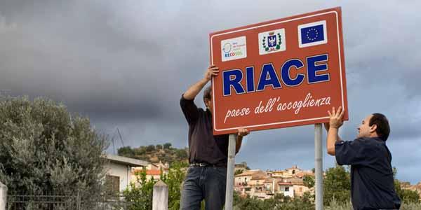 Mimmo Lucano e la targa di Riace (Foto tratta da Mediterraneo Cronaca)