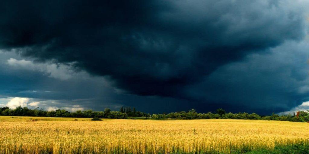 Perturbazione estiva che incombe su un campo di cereali, possibile effetto del riscaldamento globale