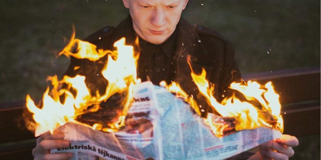 Uomo legge quotidiano che brucia, notizie sul riscaldamento globale